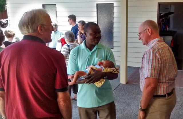 Randy talking to Issac who is holding one of his new sons.